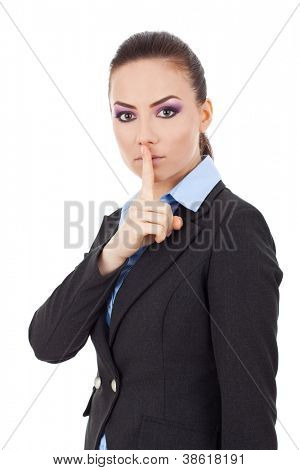 Portrait of young serious business woman keeping finger on her lips and asking to keep quiet, isolated on white background