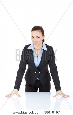 young business woman standing in front of the desk, leaning on it and smiling at the camera. isolated on white