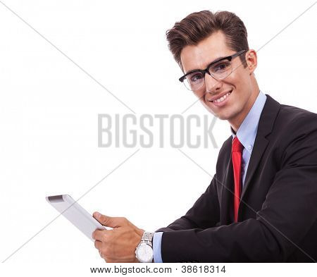 side view of a young business man holding his tablet pad and looking and smiling to the camera