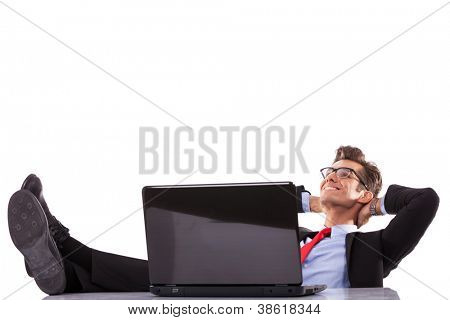 Relaxed business man working with a laptop in his office, dreaming at his success