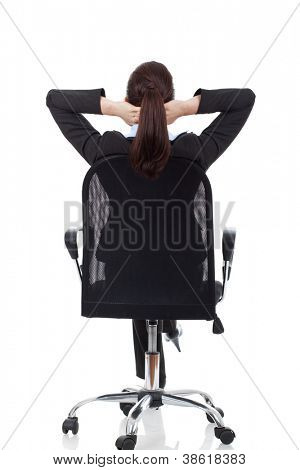 portrait of cute young business woman from behind dreaming, resting on office chair with hands behind her head