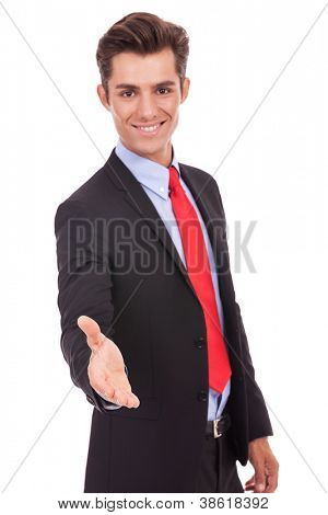 smiling young business man wlecoming you with a handshake - focus on his hand