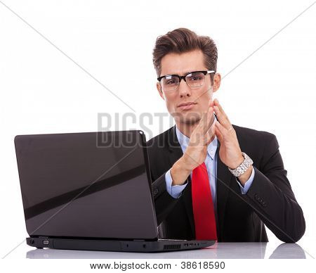 Serious executive with hands to face, looking at you, sitting at his desk with laptop