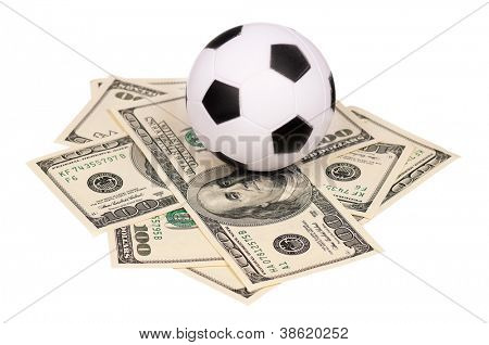 Small soccer ball on heap of dollars isolated on a white background