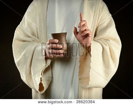 Jesus hands holding cup of wine isolated over dark background