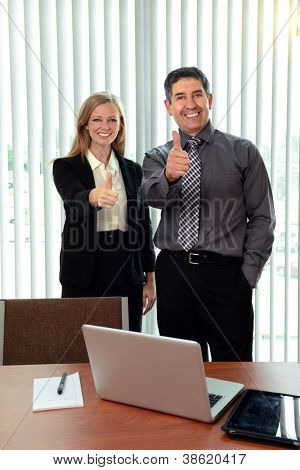Male and female office workers showing the thumbs up