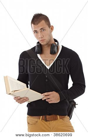 Stylish and goodlooking college student guy with book handheld, looking at camera, frowning.