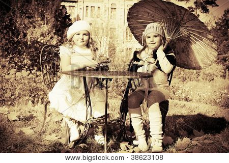 Two little girls having a rest at a park. Retro style.