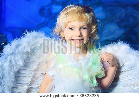 Beautiful little angel girl over Christmas background.