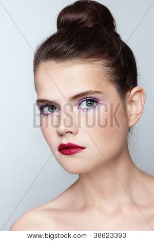 Portrait of young beautiful girl with fancy make-up and hair bun