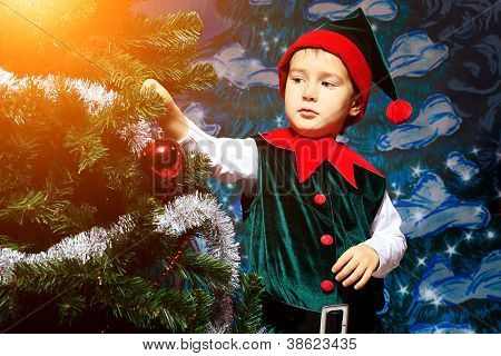 Little boy in Christmas elf costume posing over christmas background.