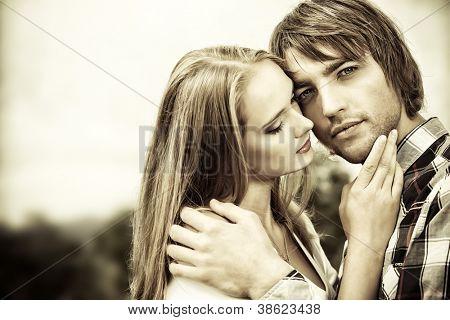 Retrato dos jovens no amor com ternura abraçando uns aos outros ao ar livre.