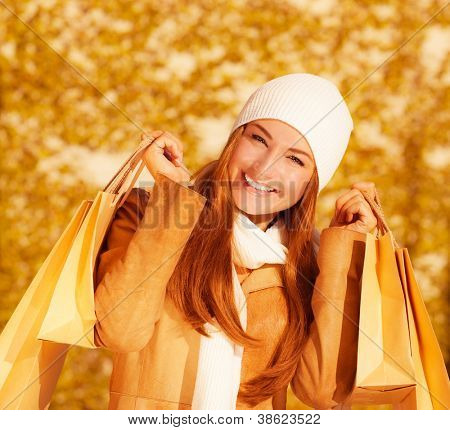 Image of attractive cheerful woman with brown shopping bags on golden autumn background, closeup portrait of happy female enjoying gift bags, spending money concept, sales season