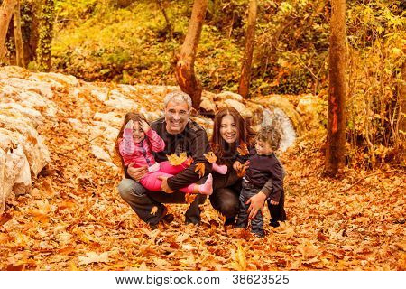 Image of beautiful female and man with cute daughter and pretty son having fun in autumnal forest, young parents with nice adorable kids playing outdoor, fall holiday, happy family concept