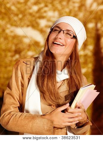 Image of beautiful student girl holding textbooks in autumn park, pretty cheerful teen female enjoying education time, cute schoolgirl resting in university garden with favorite book, back to school