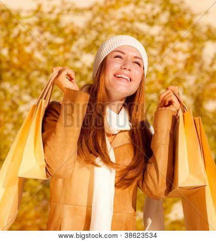 Picture of cute cheerful girl with shopping bags, attractive stylish woman rejoice her presents bags, pretty female in autumn park enjoying spending money, autumnal sales concept