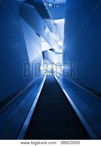 Photo of modern escalator, stairway in office building, indoors architecture, contemporary expensive design of staircase, fast move to go down, airport exit, subway station, motion up