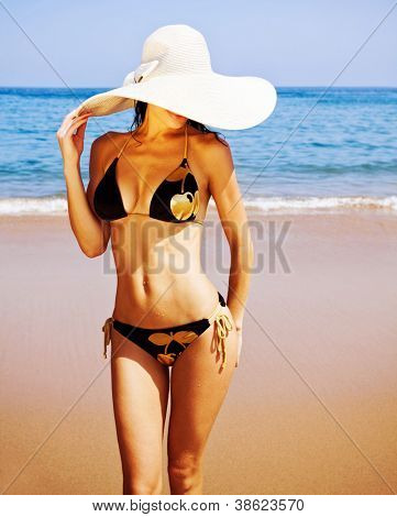 Photo of sexy woman on the beach, attractive female wearing black seductive swimsuit and big fashionable hat, healthy slim girl stand on coastline, summer holidays, luxury resort, vacation concept