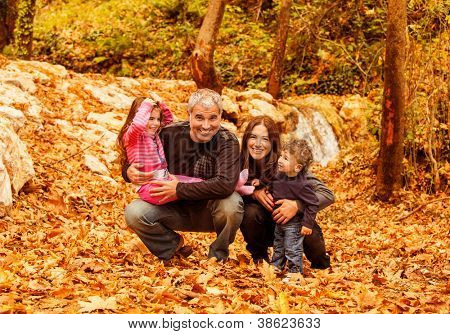 Picture of cheerful young family playing game in autumnal woods, portrait of cute kids with parents in park, autumn holidays, love concept, conceptual of happy family, fall season