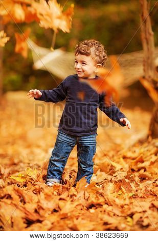 Photo of cute little boy enjoying autumnal nature, pretty infant playing in park, cheerful baby boy having fun outdoors, adorable kid in fall forest, happy child play with dry orange maple leaves
