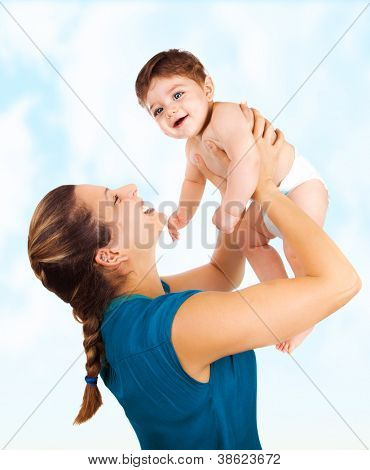 Photo of young beautiful mother with cute baby boy, smiling mommy lift her adorable son, pretty woman throwing up cheerful little child on blue sky background, happy healthy family, love concept