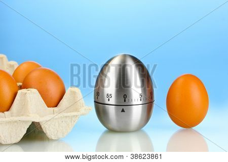 eggs in box and egg timer on blue background