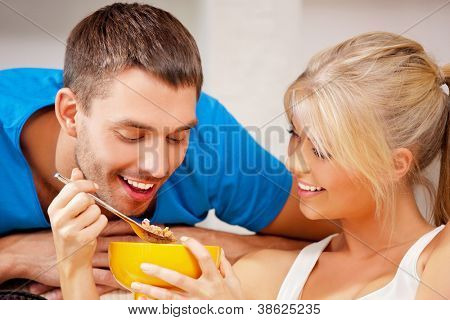bright picture of happy couple with muesli (focus on man)