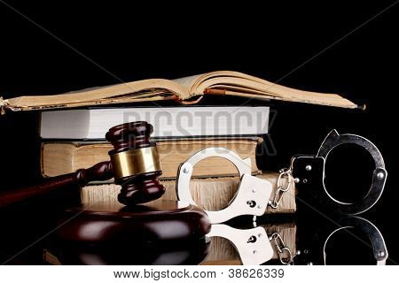 Hammer, Handschellen und Bücher über Recht isoliert auf schwarz Nahaufnahme