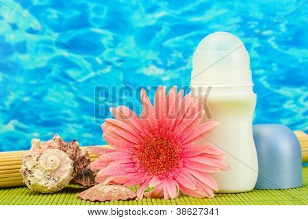 deodorant, flower and shells on blue sea background