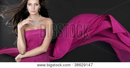 Gorgeous woman with jewellery on dark background. Banner.