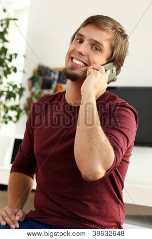 Young and happy guy with smile talking by cellphone at home