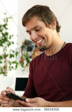 Young and happy guy using touch screen of his cell phone