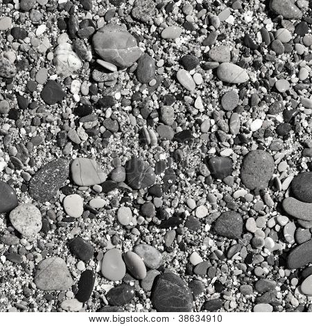 closeup of a shingle beach, with pebbles, gravel and sand in black-and-white