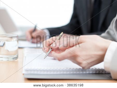 Business people writing in notebooks sitting at the office table. Close up of hands