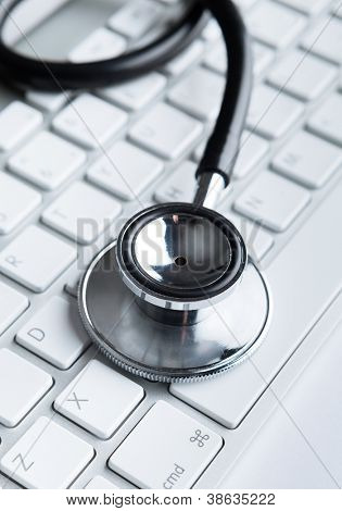 Close up of stethoscope on computer keyboard. Health concept