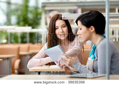 Two girls communicate sitting at the table at the reading hall. Process of communication
