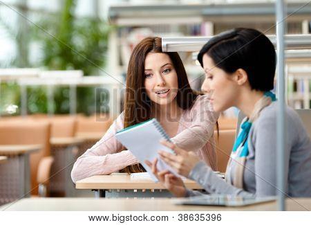 Dos chicas comunican a sentarse a la mesa en la sala de lectura. Proceso de comunicación