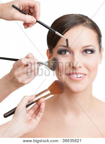 Three hands of makeup artists applying cosmetics on the woman's face with brushes, isolated on white