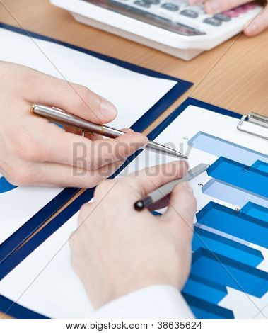 Close up shot of hands of managers discussing diagram and sitting at the table