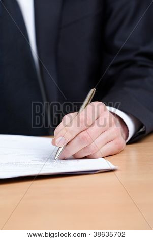 Sitting at the table businessman making notes in the notebook