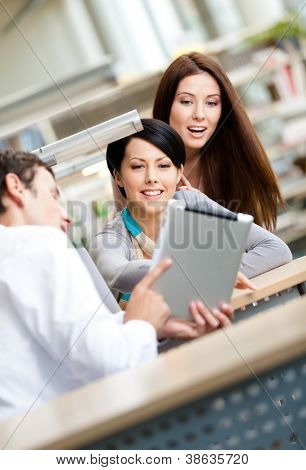 Young man sitting at the table at the library shows something interesting in the tablet to two women