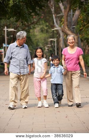 Chinese Grandparents Walking Through Park With Grandchildren