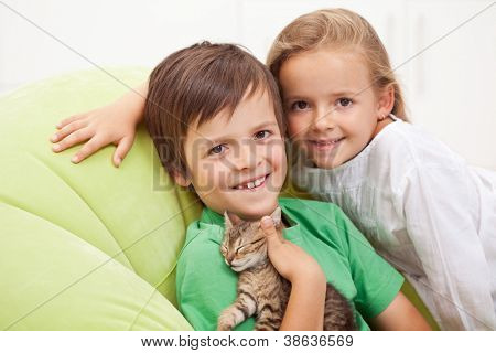 Happy kids with their new pet - a little tired kitten
