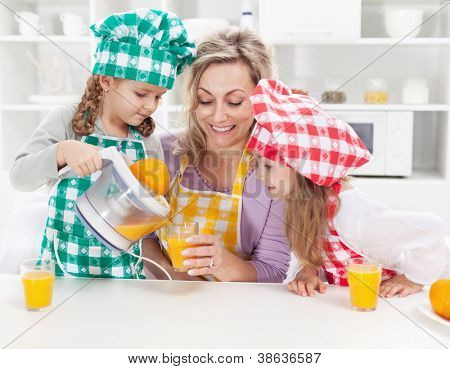 Girls and their mother making fresh orange juice in the kitchen