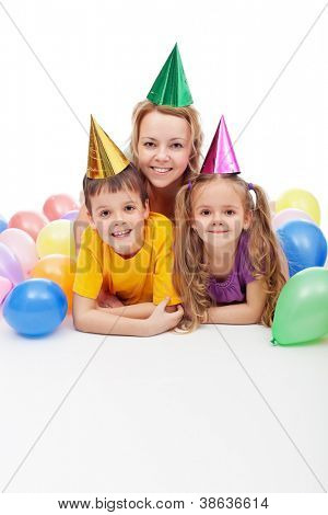 Birthday or party kids with their mother laying among colorful balloons