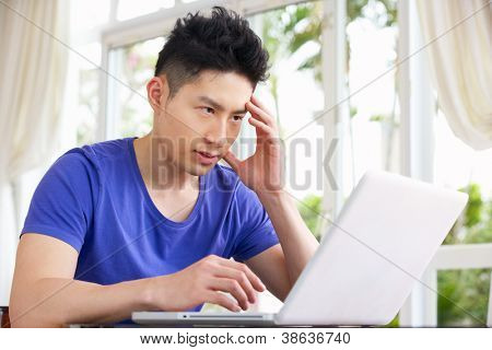 Worried Young Chinese Man Sitting At Desk Using Laptop At Home