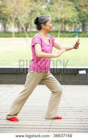 Senior Chinese Woman Doing Tai Chi In Park