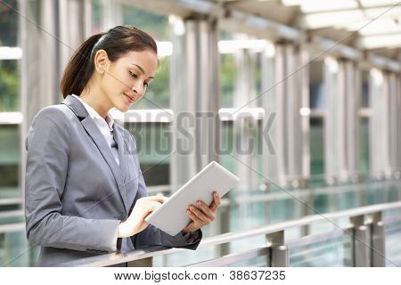 Hispanic Businesswoman Working On Tablet Computer Outside Office