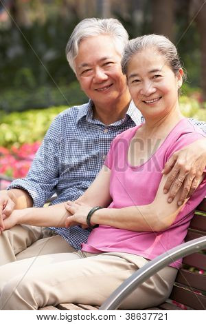 Senior Chinese Couple Relaxing On Park Bench Together