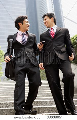 Two Chinese Businessmen Having Discussion Walking Down Steps Outside Office